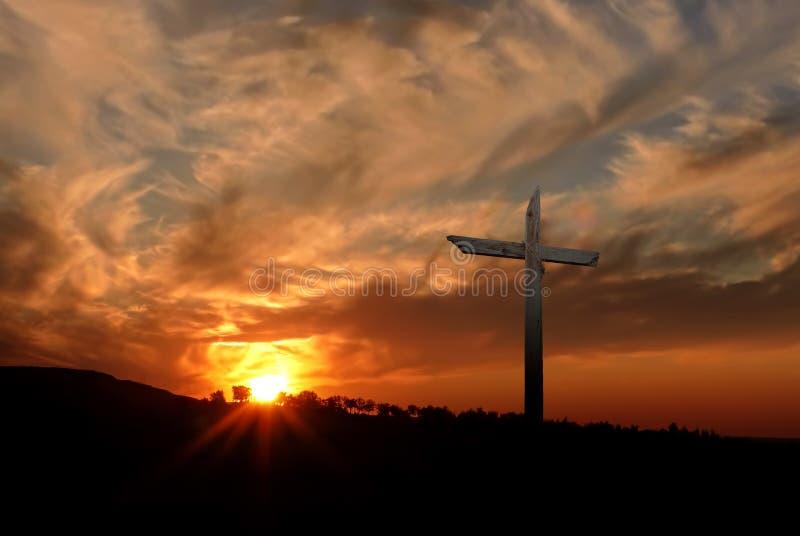 Christelijk kruis over zonsondergangachtergrond stock foto's