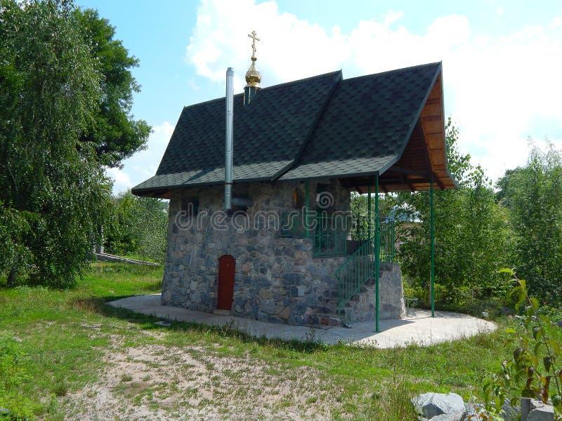 Christelijke kapel in de zomer tegen een blauwe hemel stock foto's