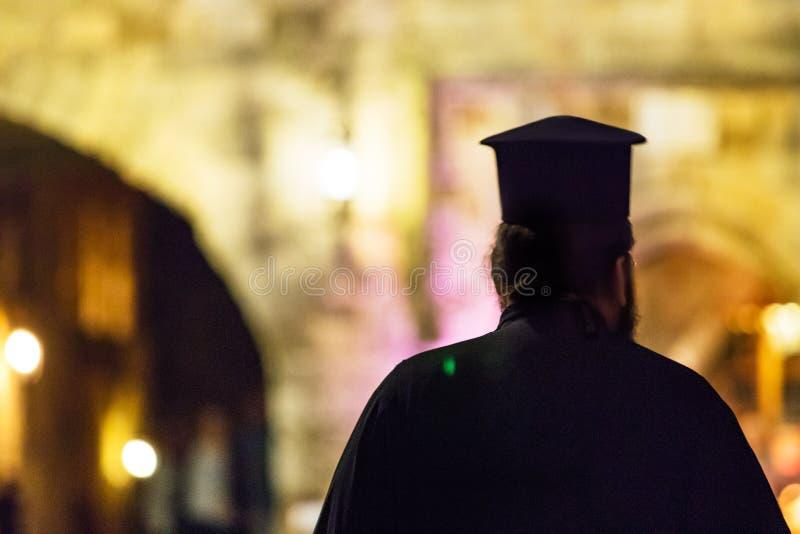 christelijke orthodoxe priester van achter het lopen alleen in de straat bij avond royalty-vrije stock afbeeldingen