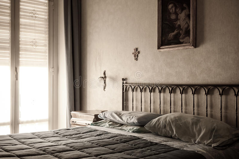 Christian bedroom. A warm light, holy cross and a picture of the nativity in a typical European style Christian bedroom stock photos