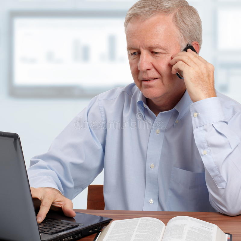 Christian busnessman. Man talking on phone in front of the laptop and the Bible royalty free stock photos