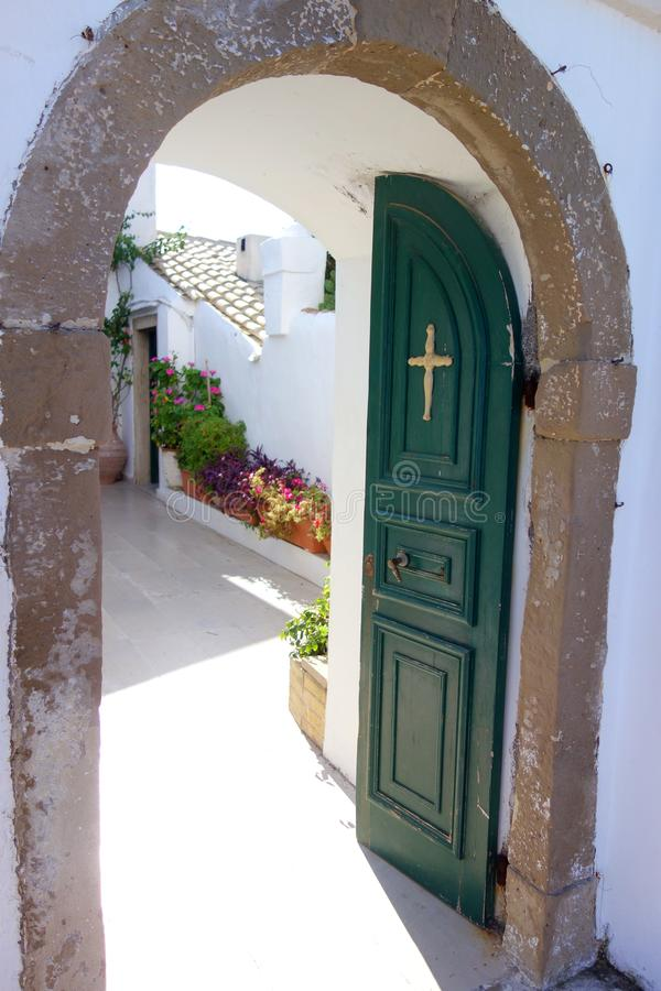 Christian church door in Greece. Open christian church green door with cross in Greece, leading to beautifl white sunny garden backyard with plant pots stock photo