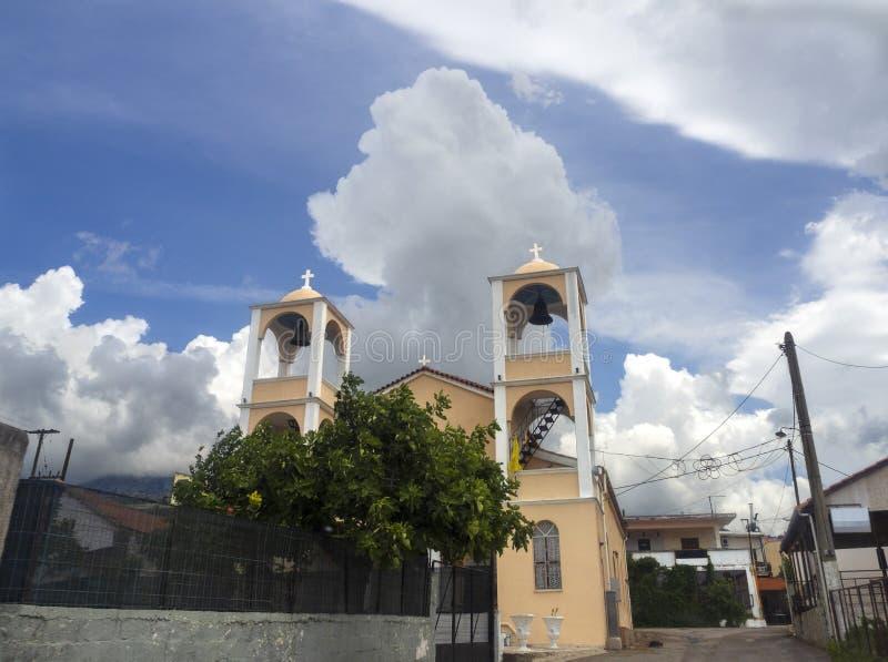 Christian Church mit einem Glockenturm im griechischen Dorf von Agios Afanasios in Evia vor dem hintergrund schöner Berge a lizenzfreies stockbild