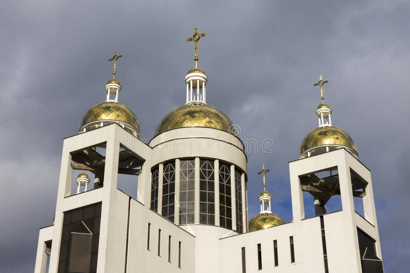 Christian church in sun light on sky background. Golden domes are shining in sunlight, evil sky before rain or bad weather. Side perspective view from ground royalty free stock photos