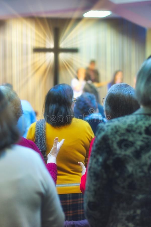 Christian congregation worship God together, with cross with light rays in background royalty free stock images