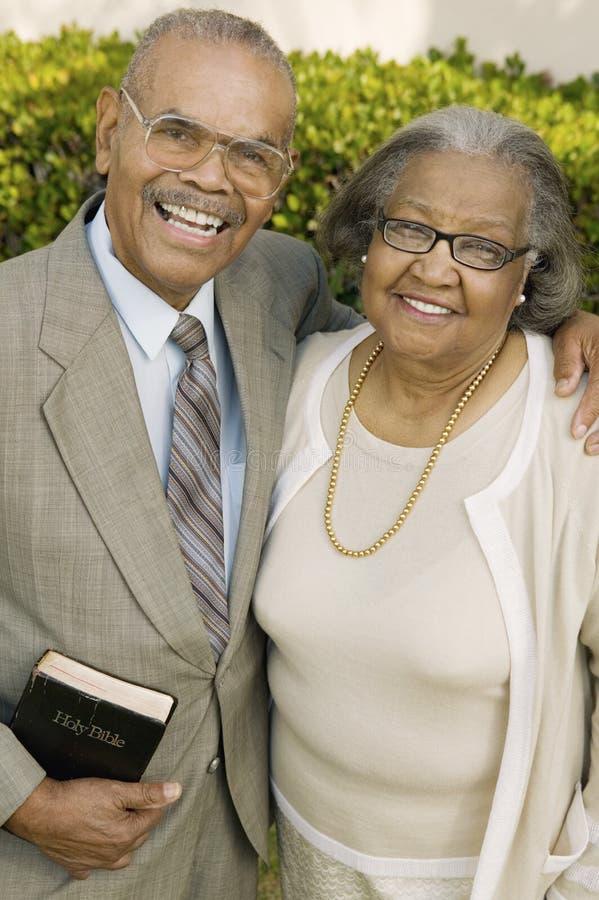 Christian Couple supérieur de sourire dans le jardin tenant le portrait de bible photographie stock libre de droits