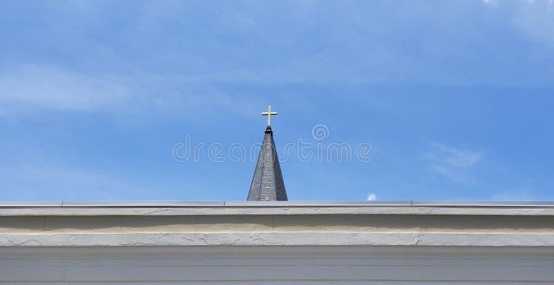 Christian Cross på kyrktorn mot blå himmel arkivfoton