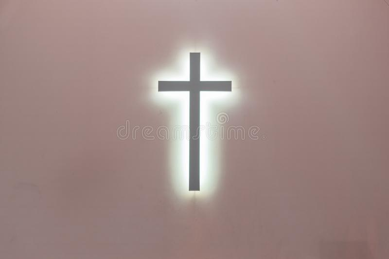 Christian cross on a pink background. a symbol of Christianity. crucifixion.  royalty free stock photos