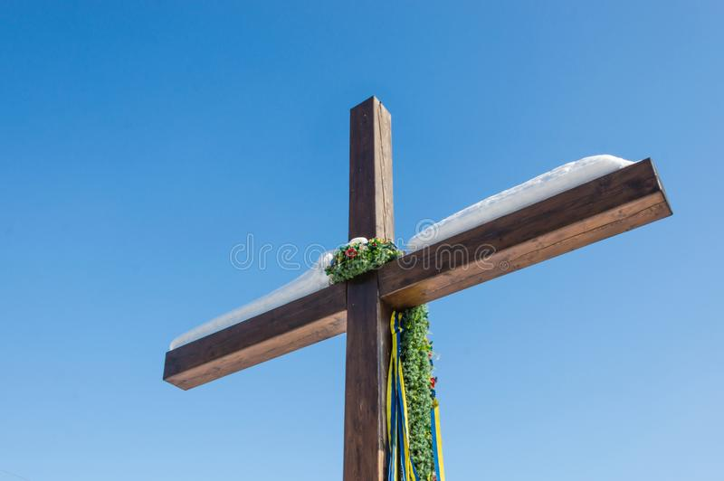 Christian cross with green wreath and ribbons on the plain blue sky background, Concept of hope, faith, love royalty free stock photography