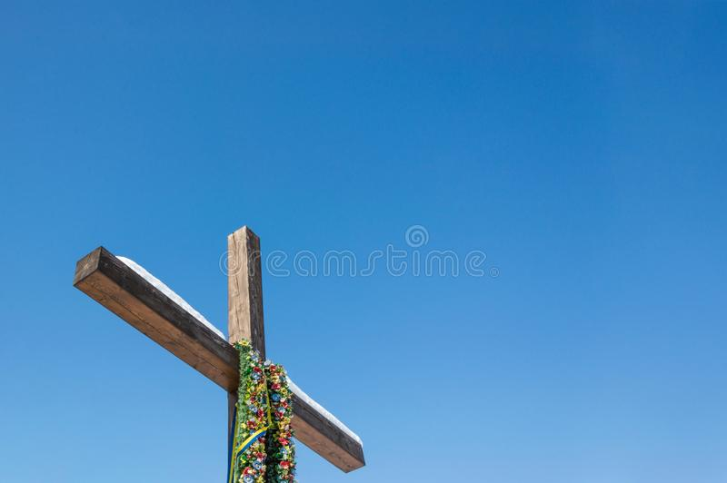 Christian cross with green wreath and ribbons on the plain blue sky background, Concept of hope, faith, love stock photography