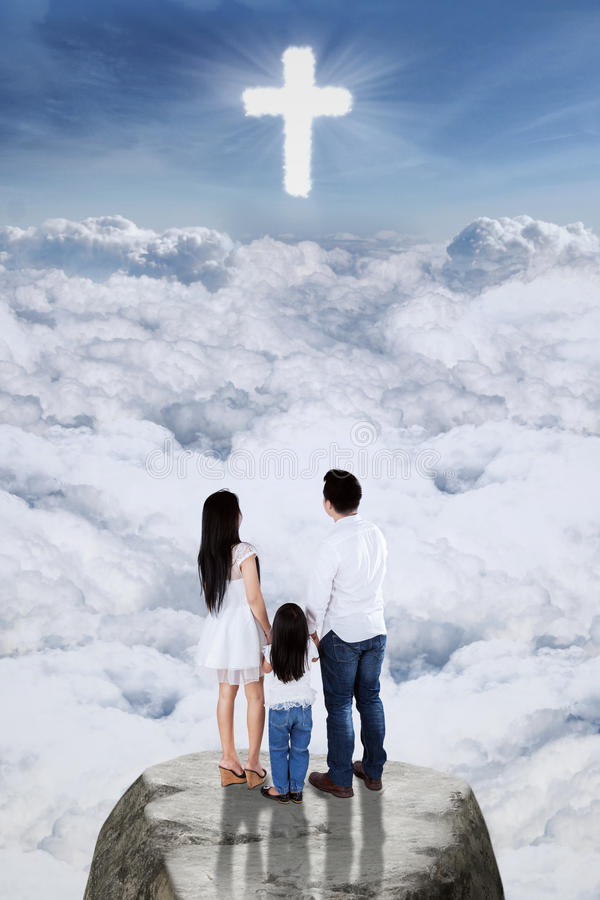Christian family looking at the cross symbol. Image of two young parents and their daughter standing on the rock and looking at the cross symbol on the sky royalty free stock photo