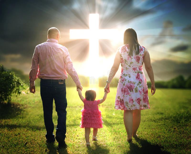Christian family walks to cross. Mother and father lead their child to a Christian cross stock image