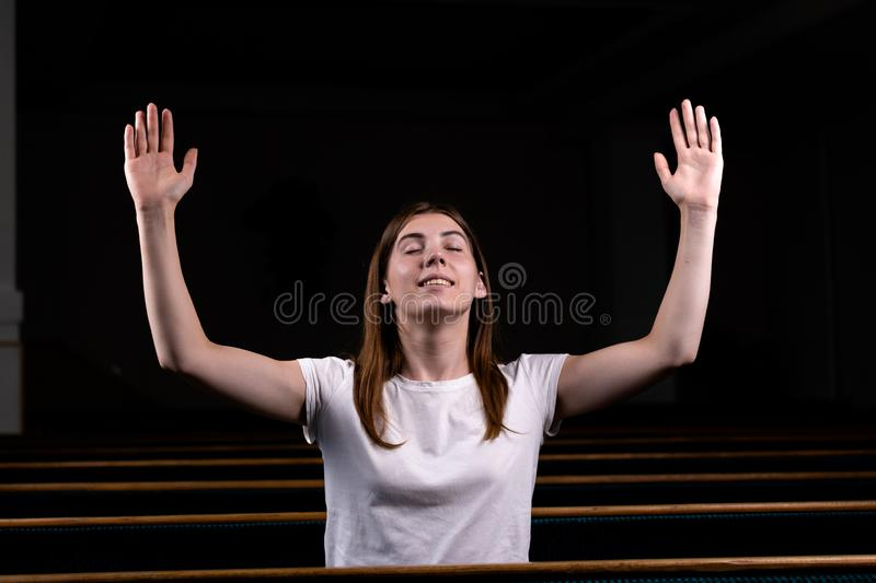 A Christian girl in white shirt is sits with his hands up and face and praying with humble heart in the church stock photo