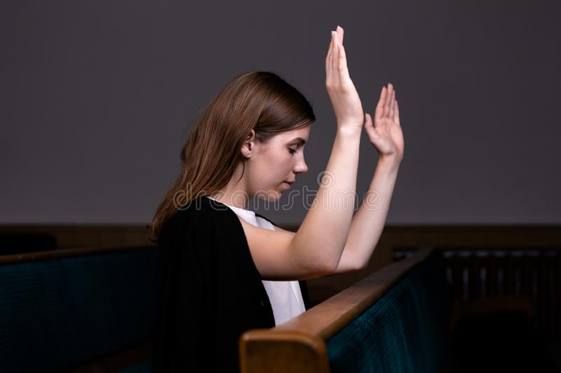 A Christian girl in white shirt is sits with his hands up and face and praying with humble heart in the church stock photography