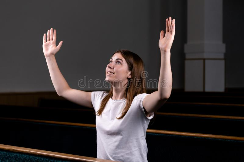 A Christian girl in white shirt is sits with his hands up and face and praying with humble heart in the church royalty free stock photos