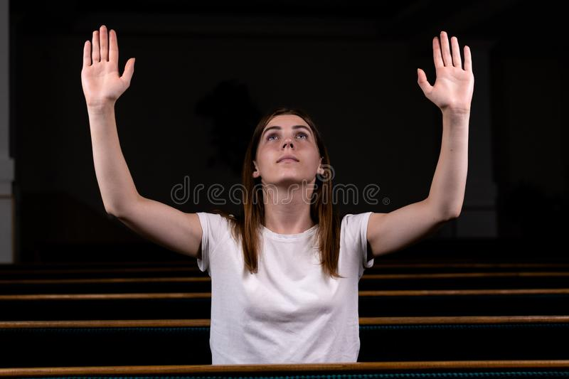 A Christian girl in white shirt is sits with his hands up and face and praying with humble heart in the church stock photos