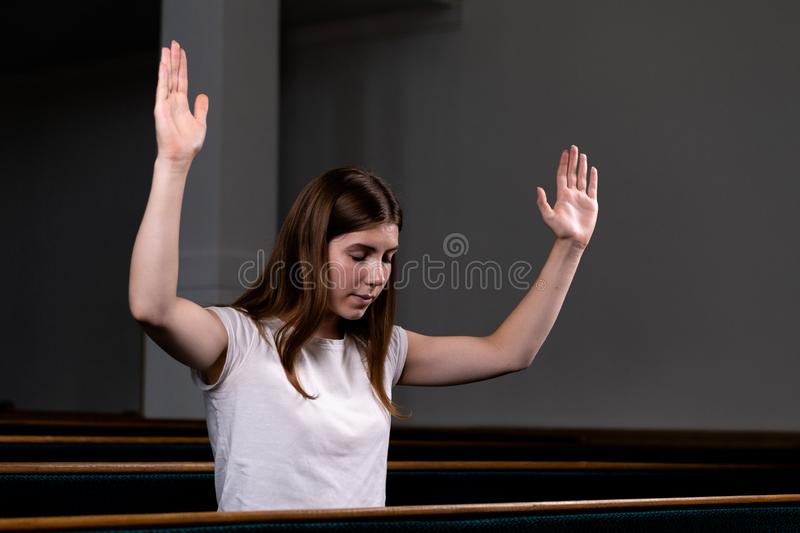 A Christian girl in white shirt is sits with his hands up and face and praying with humble heart in the church royalty free stock photo