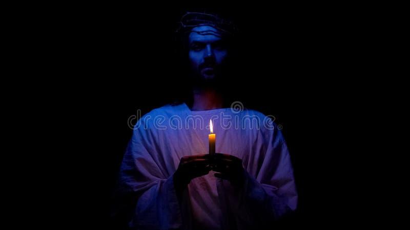 Christian God in Dornenkrone Kerze in der Dunkelheit halten betend für Leute stockbild
