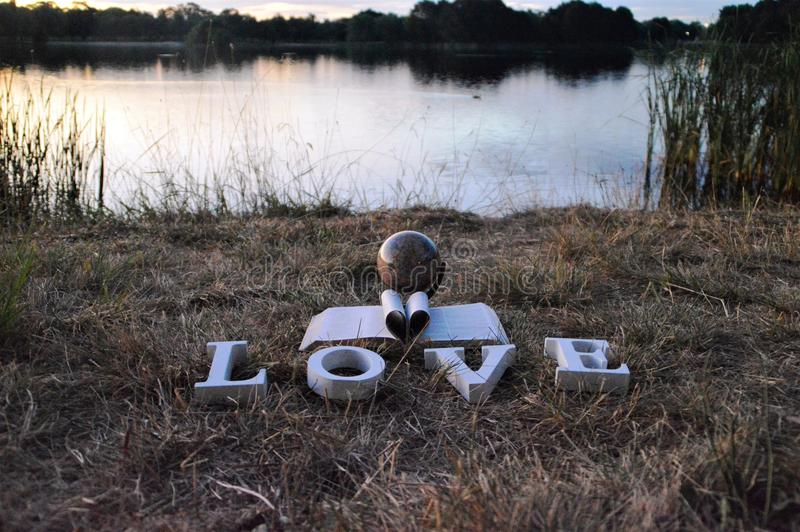 Christian love. A book heart made from pages of the Bible and the word `love` in white letters can be seen sitting in front of a globe of the world. The photo royalty free stock image