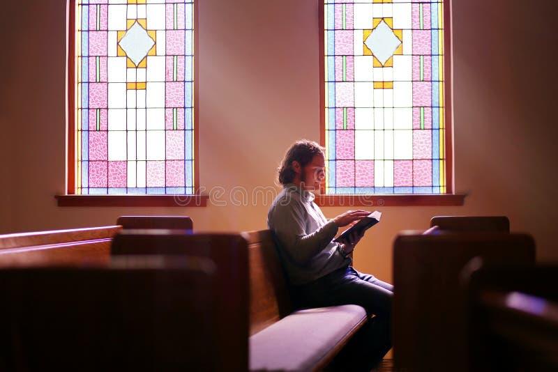 Christian Man Sitting Alone in banco di chiesa vuoto scuro della chiesa dalla finestra di vetro macchiato luminosa immagine stock libera da diritti