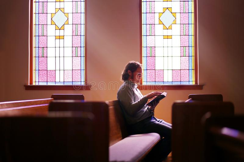 Christian Man Sitting Alone in Dark Empty Church Pew by Bright Stained Glass Window royalty free stock image