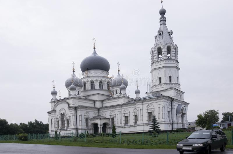 Christian orthodox white church with silver and grey domes with gold crosses. Calm grey sky above stock photography