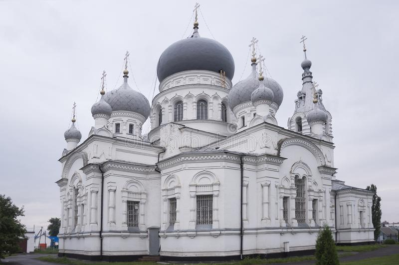 Christian orthodox white church with silver and grey domes with gold crosses. Calm grey sky above stock photo