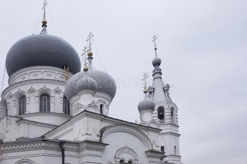 Christian orthodox white church with silver and grey domes with gold crosses. Calm grey sky above royalty free stock images