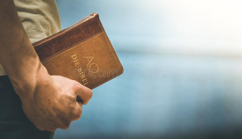 Christian preacher: Young man is holding the bible, praying stock photography