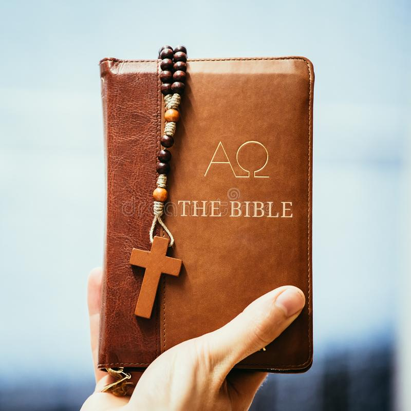 Christian preacher: Young man is holding the bible, praying royalty free stock photos
