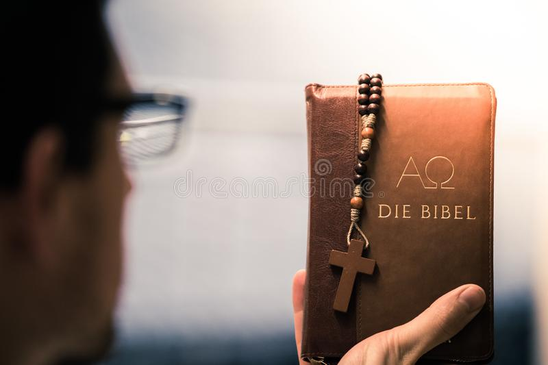 Christian preacher: Young man is holding the bible, praying stock photos