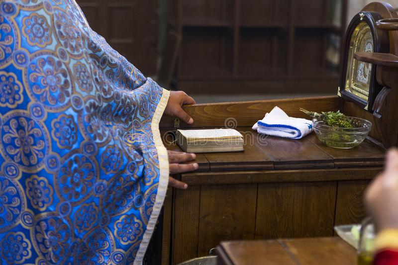 A Christian priest during a liturgy, wedding or baptism in a small church. Natural light in a small Christian church and a light grain effect stock images