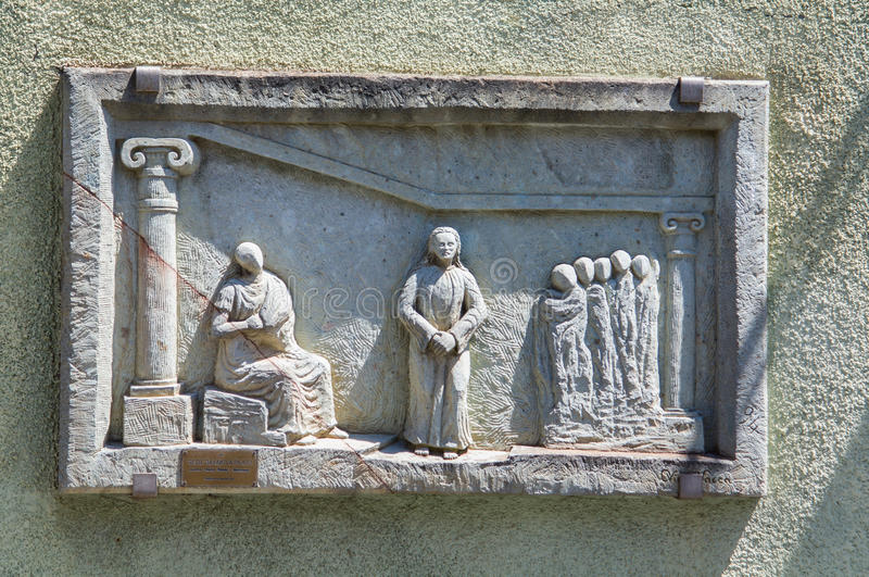 Christian religion. Passion of Christ. Via Crucis, first station: Jesus is condemned to death. Artistic bas-relief on stone installed on wall to mark the first stock photos