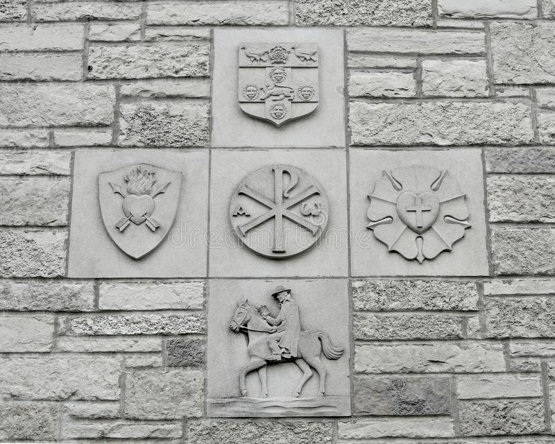 Christian Religious Symbols on Stone Wall Background. Located on the e of the Baker Memorial United Methodist Church in Saint Charles, Illinois. Shield, heart stock photography