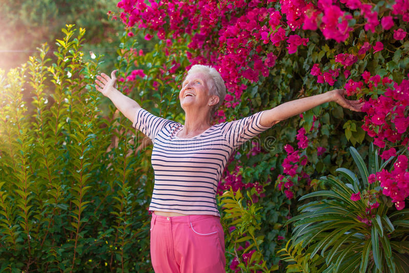 Christian senior woman arms outstretched with praise royalty free stock photos