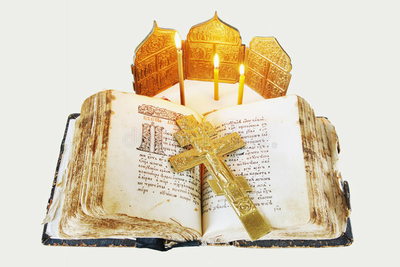 Christian still life with an open ancient book and crucifixion. Orthodox Christian still life with an open ancient book and metal crucifixion on light background stock photography