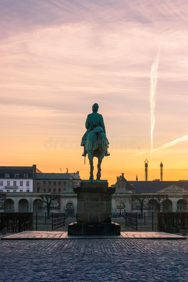 Equestrian statue of Christian IX in Copenhagen. Christiansborg Equestrian statue of Christian IX in Copenhagen at sunset, in the background Tivoli royalty free stock images