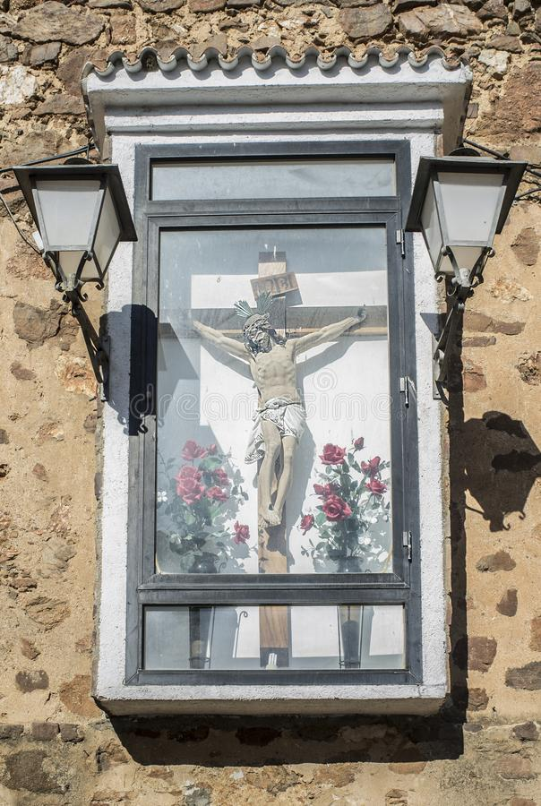 Christliches Kruzifix steht eingehüllt und draußen zur Wand befestigt stockfoto