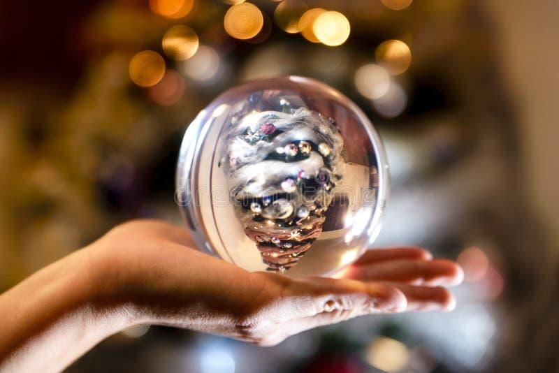 Christmansboom in een bal boven één hand stock foto