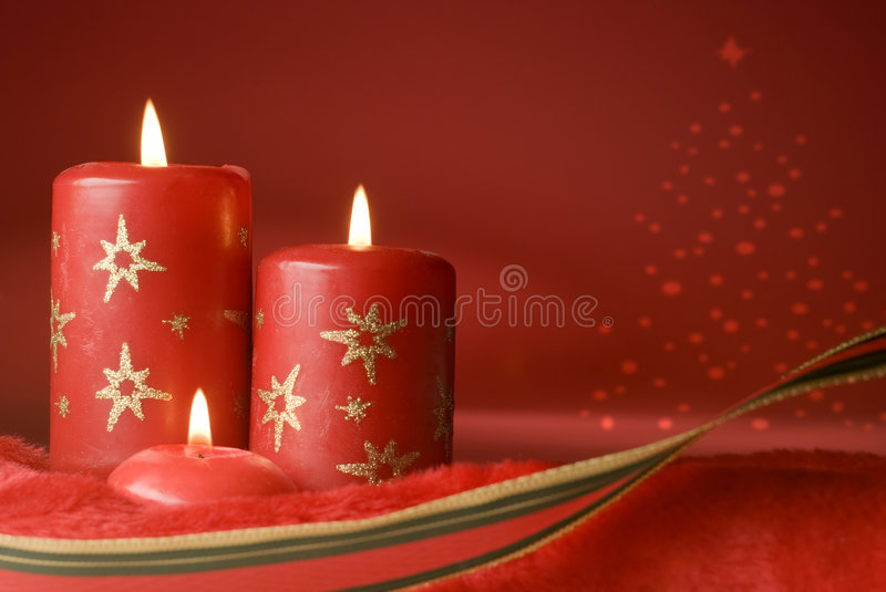 Christmas. Three red christmas candles on red background