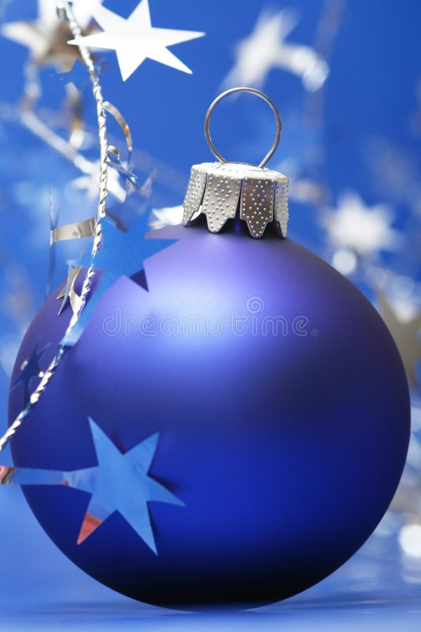 Christmas. Blue ball on blue background with silver stars stock images