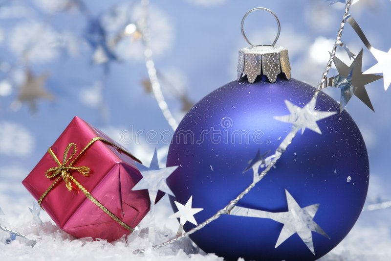 Christmas. Blue ball on blue background with silver starsand smal gift royalty free stock images