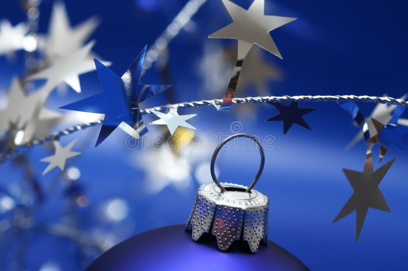 Christmas. Blue ball on blue background with silver stars stock photos