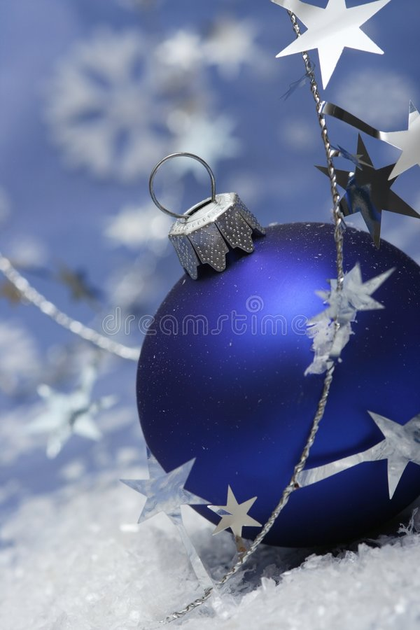 Christmas. Blue ball on blue background with silver stars stock photography