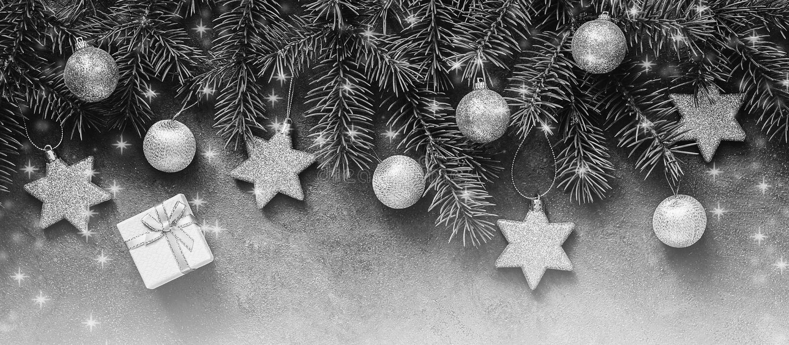 Christmas abstract border in black and white with a silver tone, fir branches decorated with balls and stars. Top view, flat lay royalty free stock images