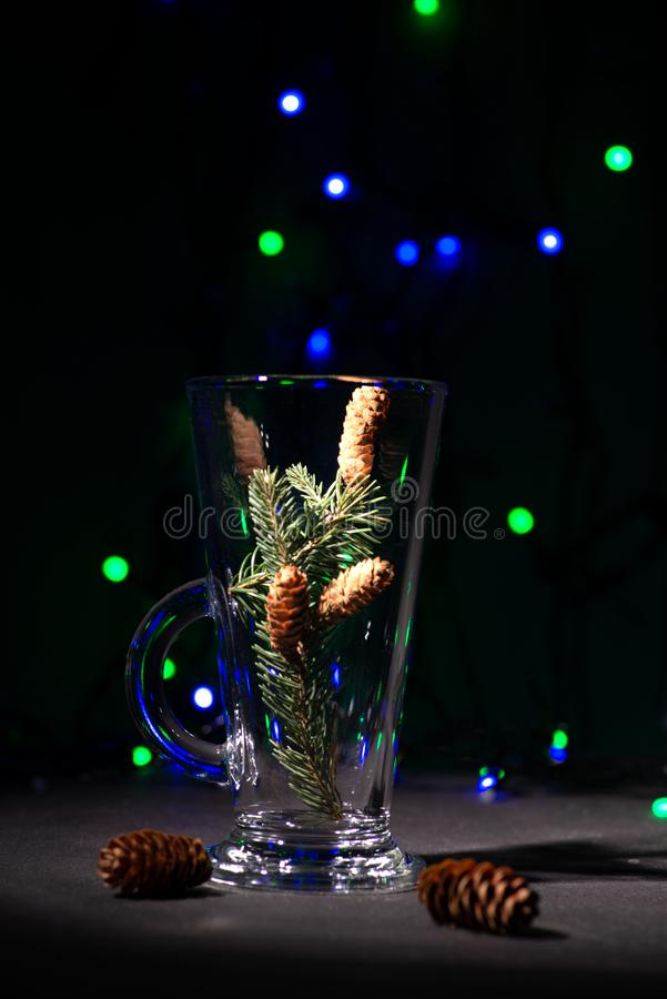 Christmas abstraction. A fir-tree branch with cones in a glass. On the reflecting black surface. In the distance multi-colored garlands sparkle, copy space royalty free stock photos