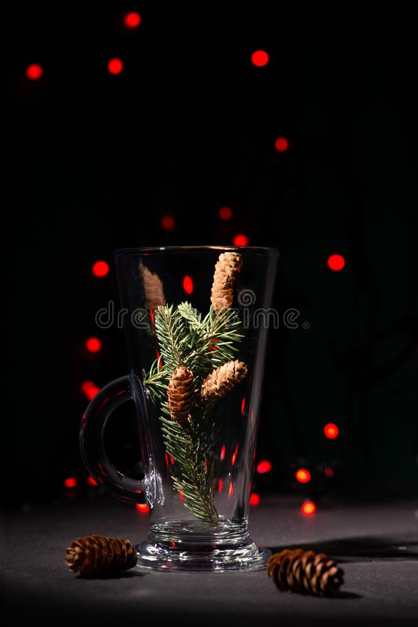 Christmas abstraction. A fir-tree branch with cones in a glass. On the dark background in studio. In the distance red garlands sparkle, copy space royalty free stock images