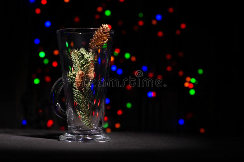 Christmas abstraction. A fir-tree branch with cones in a glass. On the reflecting black surface. In the distance multi-colored garlands sparkle, copy space stock photo