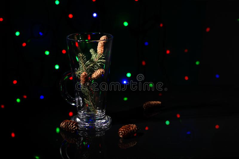 Christmas abstraction. A fir-tree branch with cones in a glass. On the reflecting black surface. In the distance multi-colored garlands sparkle, copy space stock photos