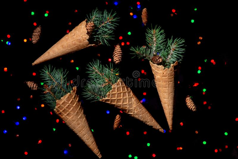 Christmas abstraction. A fir-tree branch with cones in a waffle. Cups on the black surface. In the distance red garlands sparkle stock photo